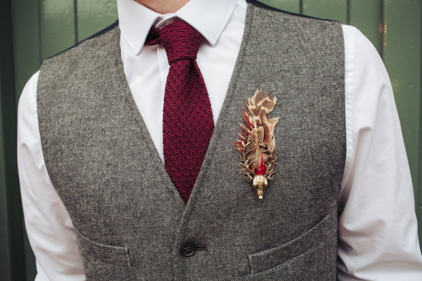 Groom wears grey wool waistcoat with burgundy tie and stag and feather brooch