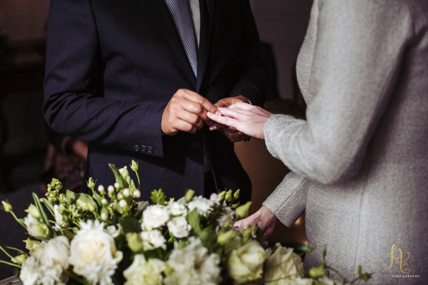 Groom places wedding ring on the brides finger