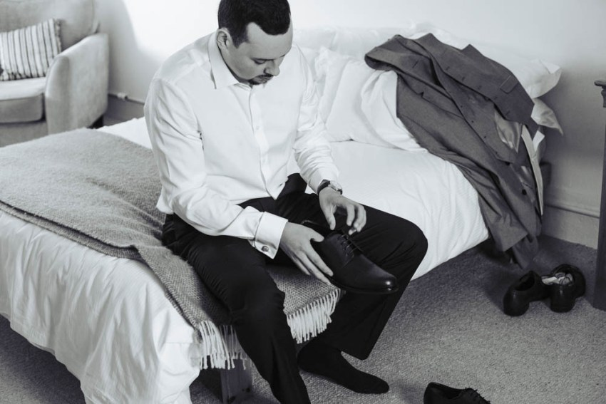 Groom sat on bed putting his shoes on