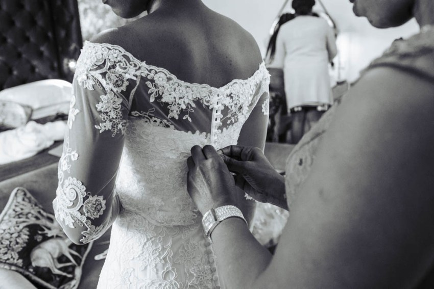 Brides mother fastens back of the bride's lace wedding dress