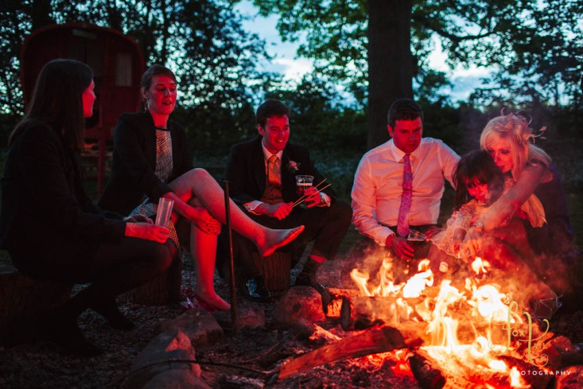 Wedding guests sit around the camp fire at alternative glamping wedding venue, Markington Hall in North Yorkshire.