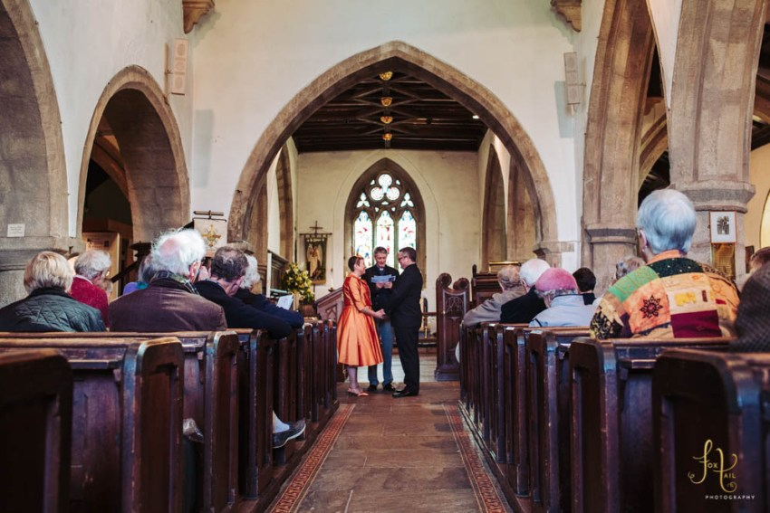 Bride wears orange dress for renewal of wedding vows. at Linton St. Michael's church in Grassington, North Yorkshire.