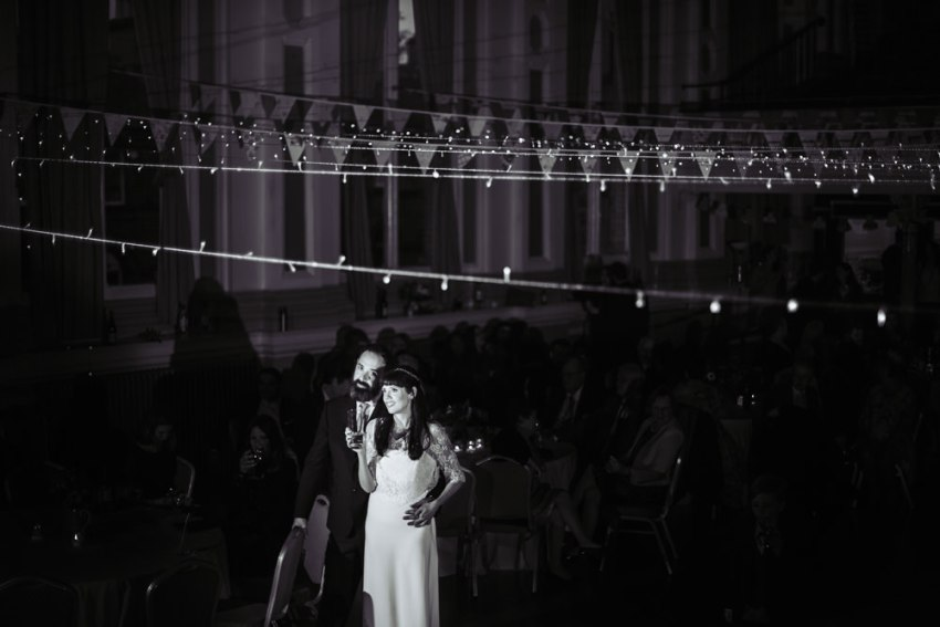 Bride and groom hold each other while listening to the band play. Victoria Hall wedding photography at Saltiare in Yorkshire.