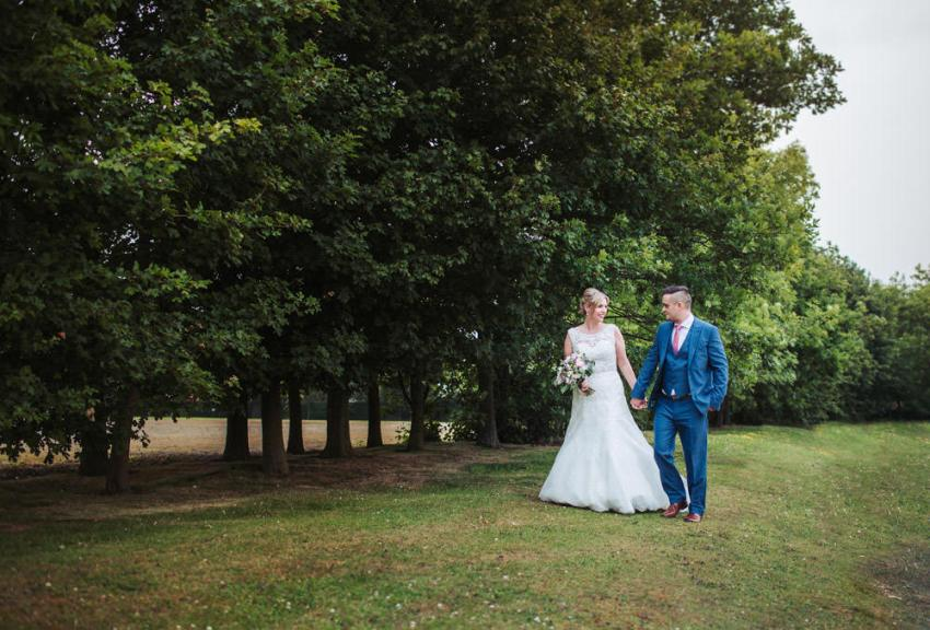 Harrogate Pavilion wedding photographer North Yorkshire. Natural photography portrait of bride and groom walking among the trees.