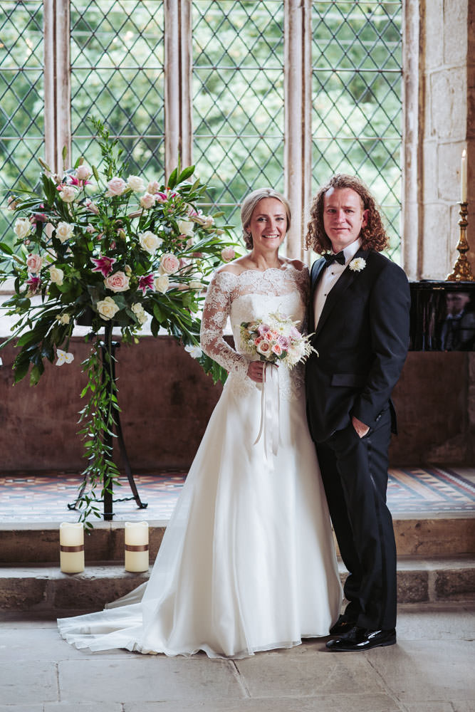 Couture lace brides dress by Chanticleer brides. Groom wears tuxedo. Medieval setting of the Priests House, a Barden Tower wedding, near Bolton Abbey in Skipton. By Yorkshire wedding photographer UK.