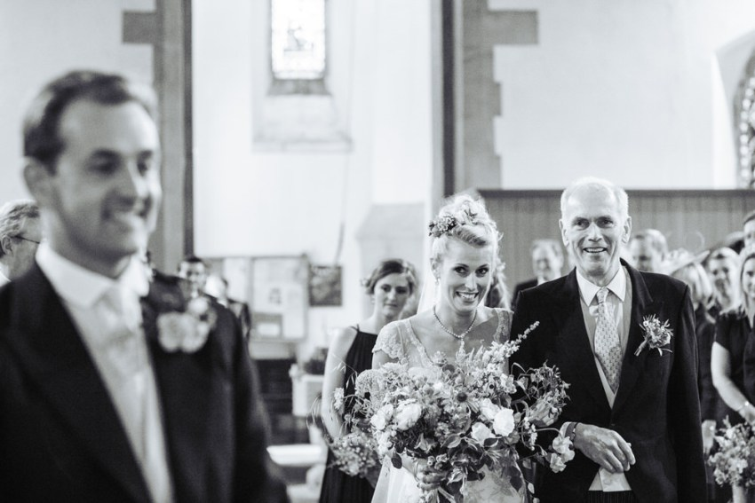 Bride walks up the isle of All Saints Church in Staveley in York.