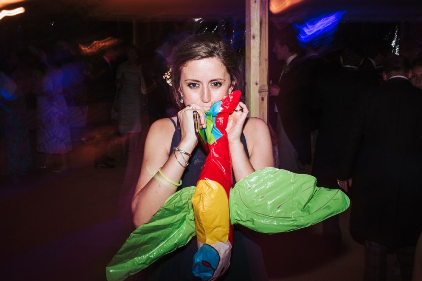 Reportage photography York UK. Bridesmaid blows up inflatable parrot.