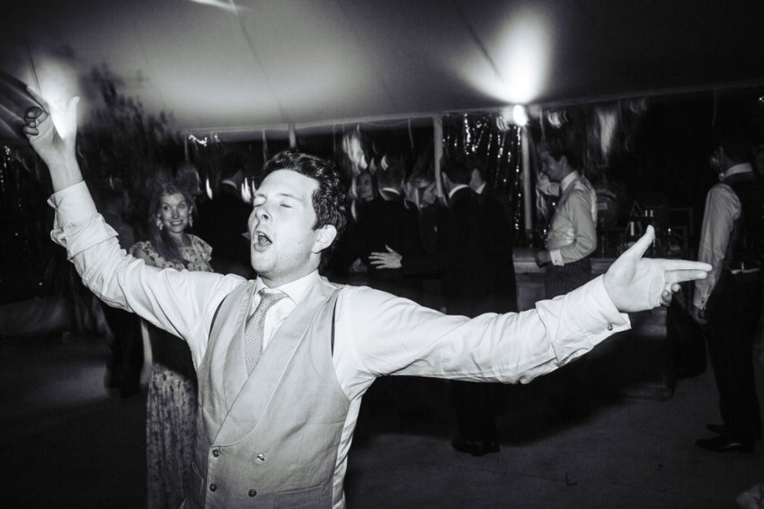 Candid dance floor photography. Male guest sings and dances.