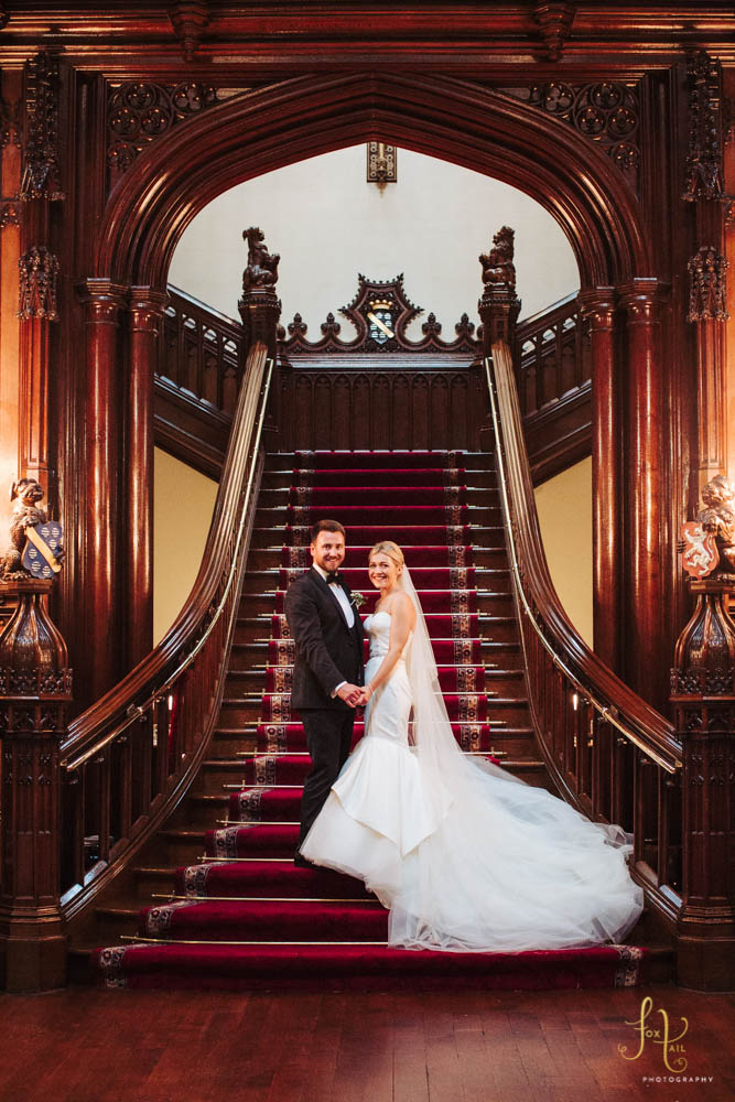 Bride and groom on gothic staircase in grand hall at Allerton Castle.