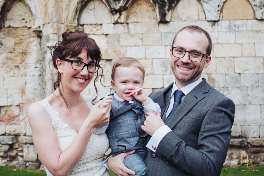 Bride and groom portrait with their baby son.