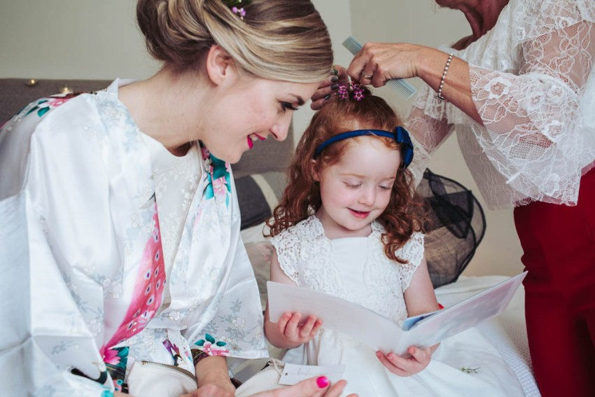 Flower girl reads card from bride while having hair done.