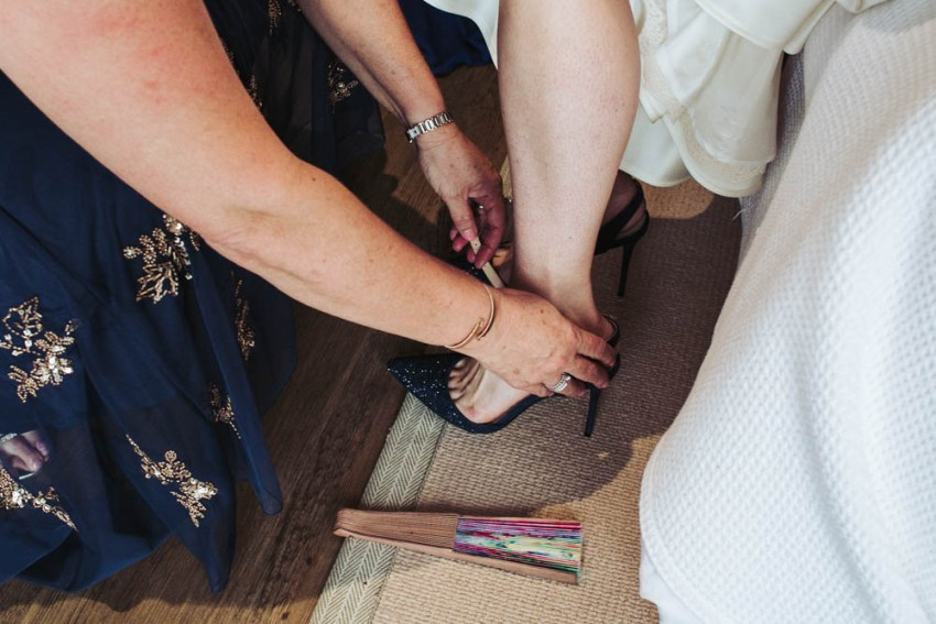 Mum helps bride into blue shoes.