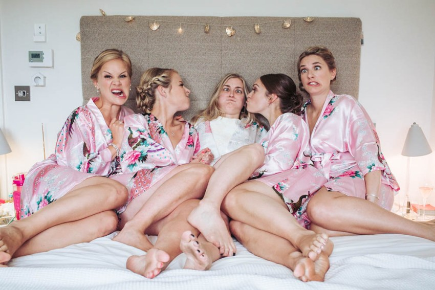 Bride on bed with bridesmaids wearing pink kimono style dressing gowns pulling faces.