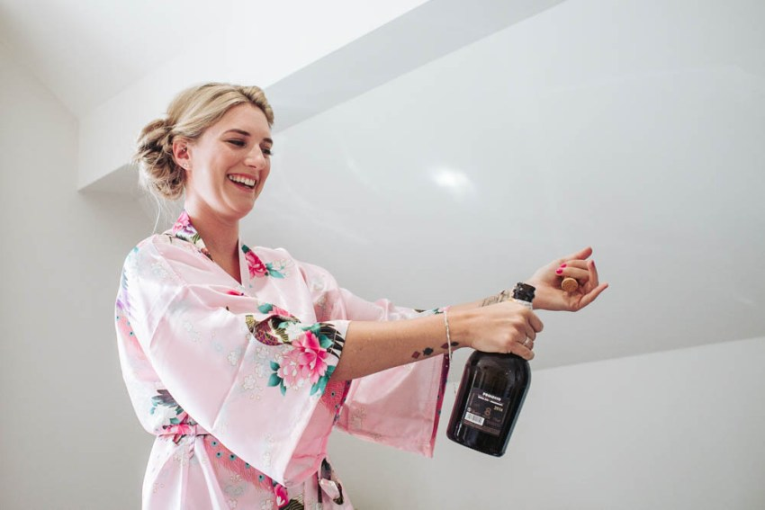 Bridesmaid in pink kimono style dressing gown opens bottle of champaign.
