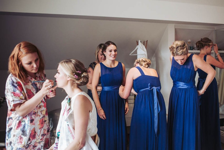 Bridesmaids dressing in royal blue dresses while bride has makeup done at Brocco on the Park Sheffield.
