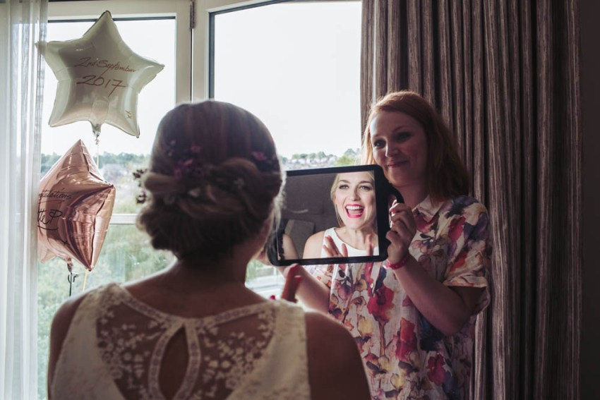 Bride seeing her makeup for first time in mirror.
