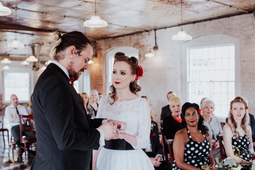 Rockabilly couple exchanging rings at industrial mill venue.