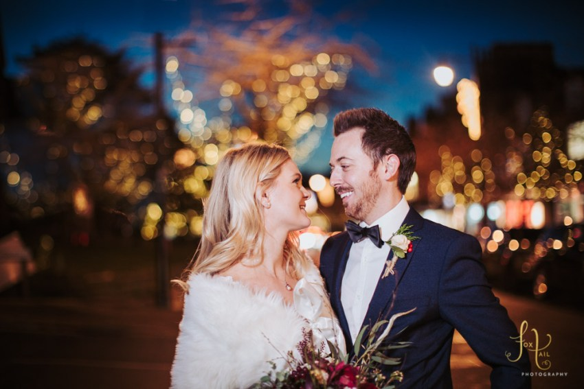 Kings Hall & Winter Gardens wedding photographer | Bride and groom photography in Ilkley, Leeds, with Christmas light backdrop.