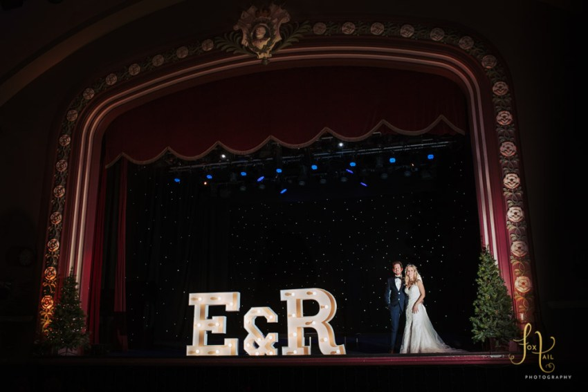 Kings Hall & Winter Gardens wedding photographer, Ilkley, Leeds | Bride and groom photography with light up letters on the theatre stage.