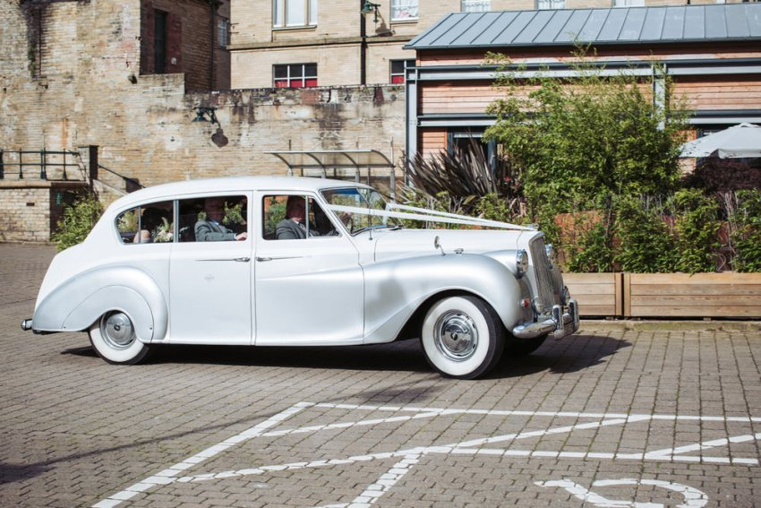 Bride arrives at Yorkshire wedding venue in a vintage silver Rolls Royce car.
