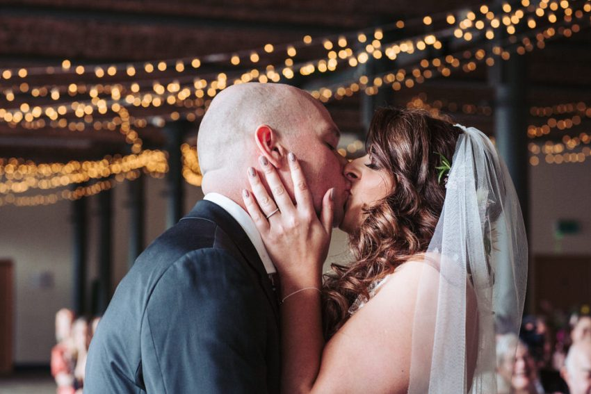 Bride and grooms first kiss with fairy light backdrop.