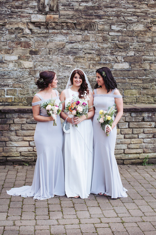 Bride wearing beautiful Rembro Styling Byork dress with bridesmaids in grey.