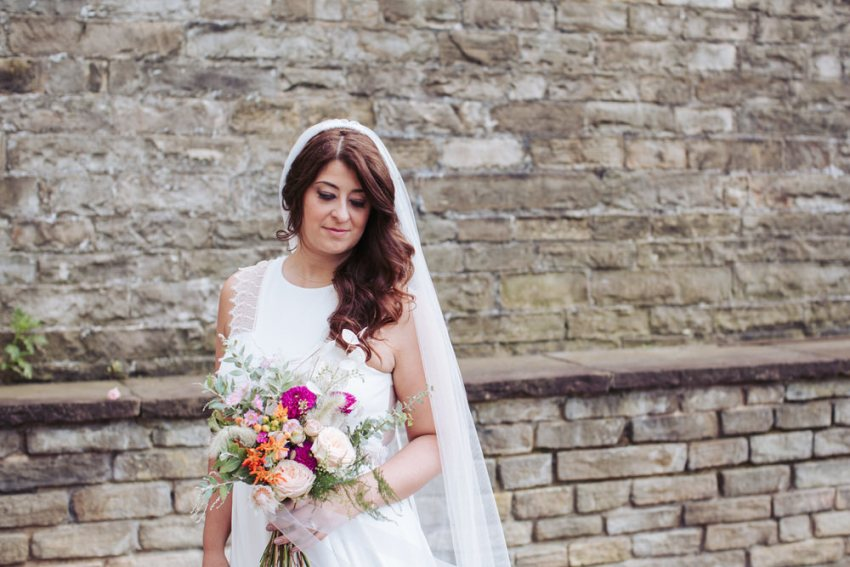 Portrait of bride wearing Rembro Styling Byork dress and holding a bouquet.