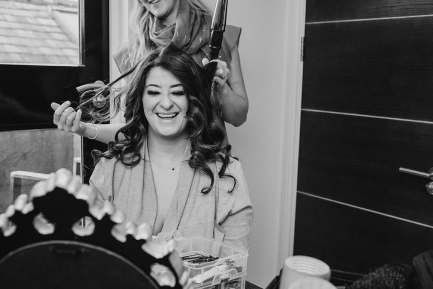 Bride having hair curled by Anna Stephenson.