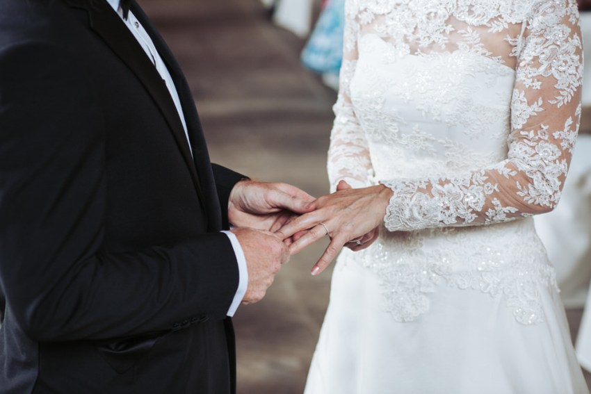 Bride and groom exchange rings during wedding ceremony. Bride in lace dress.