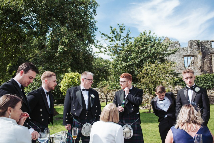 Male wedding guests wearing kilts and tuxedos, enjoying a drink on the lawn at the Priest House.