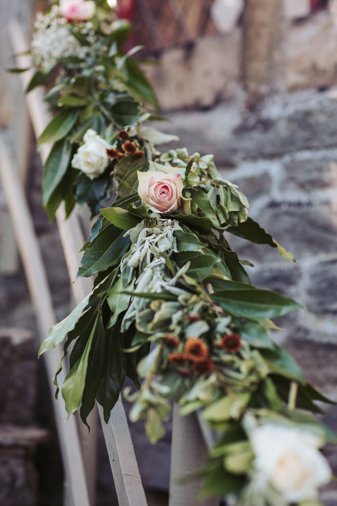 Rose and bay wreath decorates an outdoor banister.