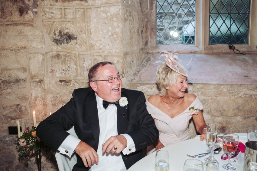 Guest laugh during speeches. Man wears a tuxedo with lady in pink dress.