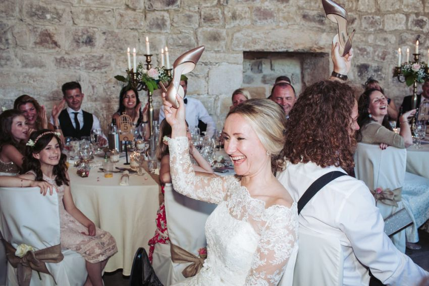 Bride and groom play quiz answering questions using shoes. Bride laughing.