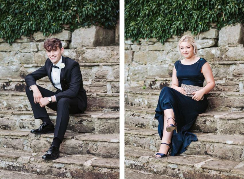 Portrait of best man and brides maid on steps. Best man wears a black tuxedo, bridesmaid wears a dark blue dress.