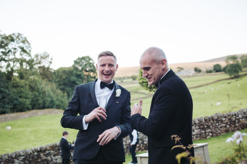 Men wearing tuxedos laugh. Green fields in background.