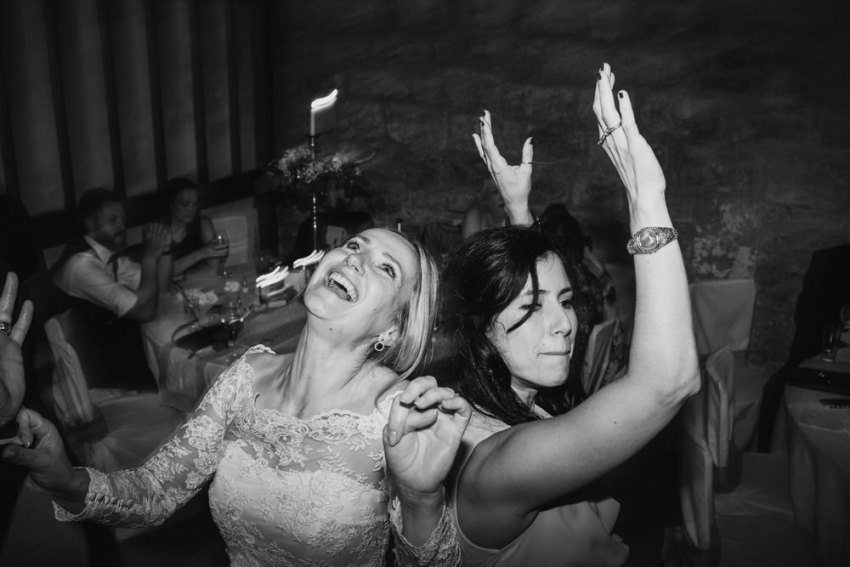 Bride dances with a friend, smiling with hands in the air.