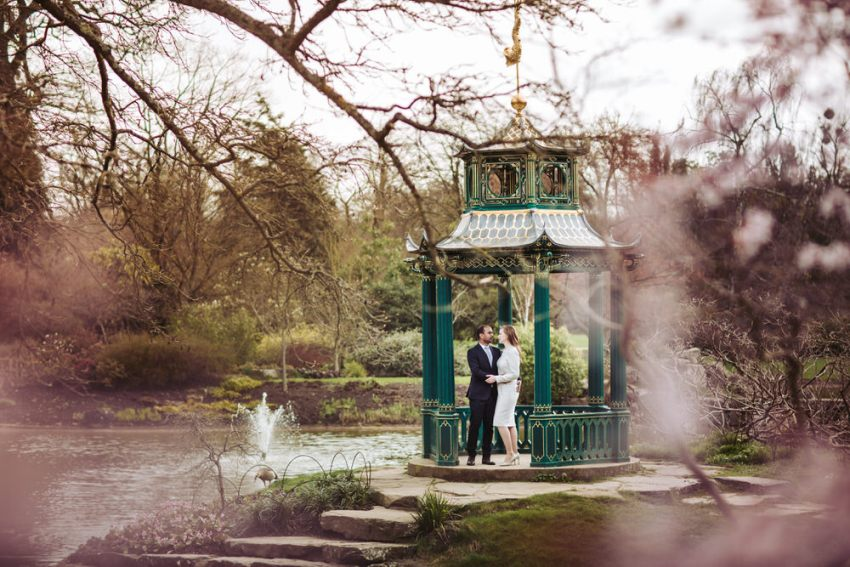 Bride and groom stand in the pergola at Cliveden House gardens.