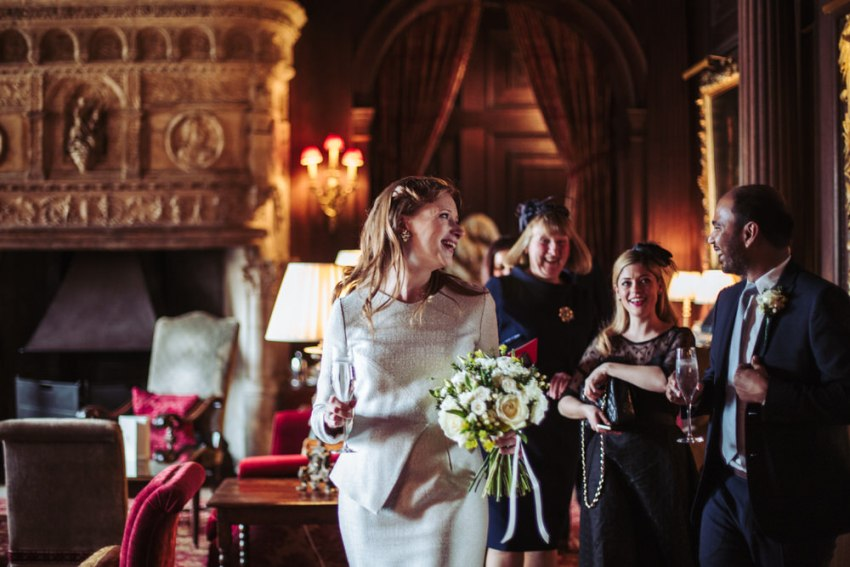 Bride and groom walk through the grand hall at Cliveden House hotel.