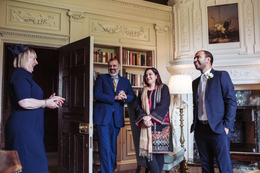 Guests laugh during wedding drinks reception at Cliveden House.