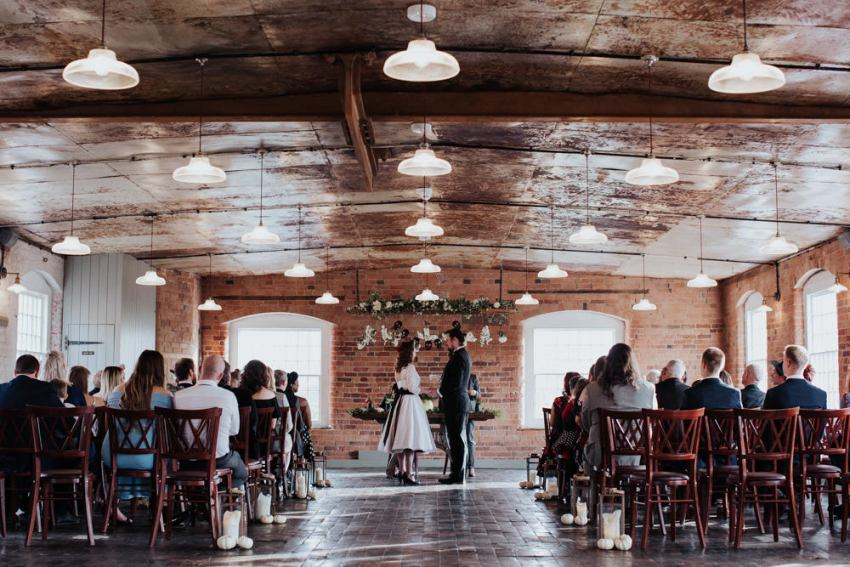 Wedding ceremony in an industrial mill venue.