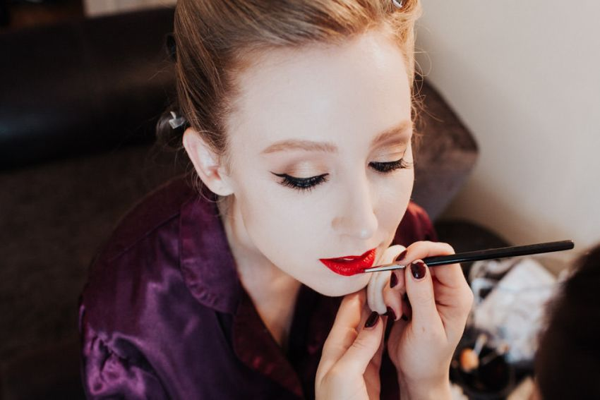 Brides application of red lipstick by makeup artist.
