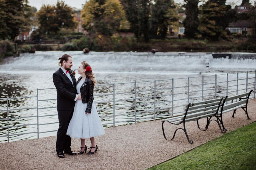 Rockabilly wedding. Bride and groom stood by a river.