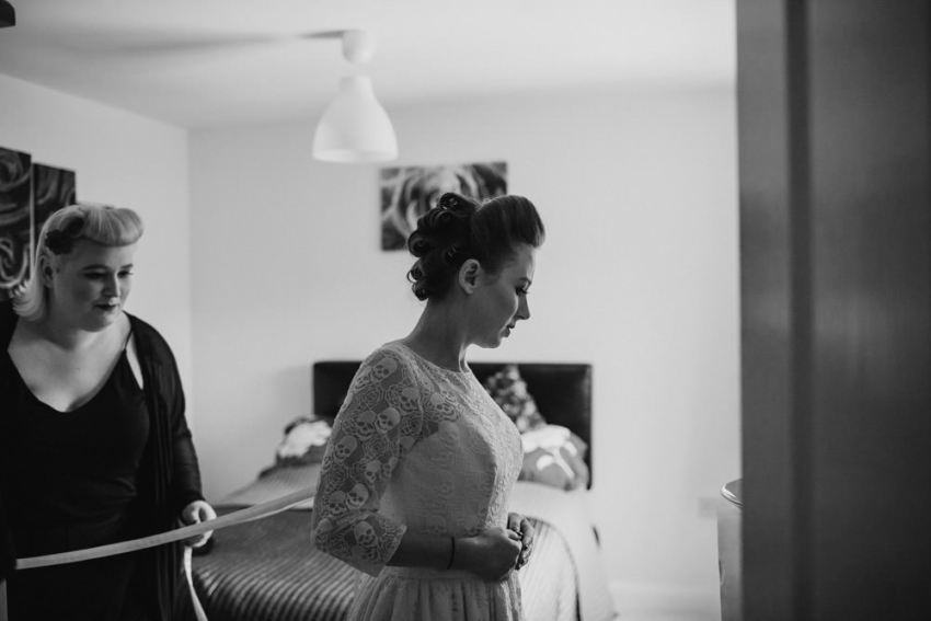 Bride being laced into dress.