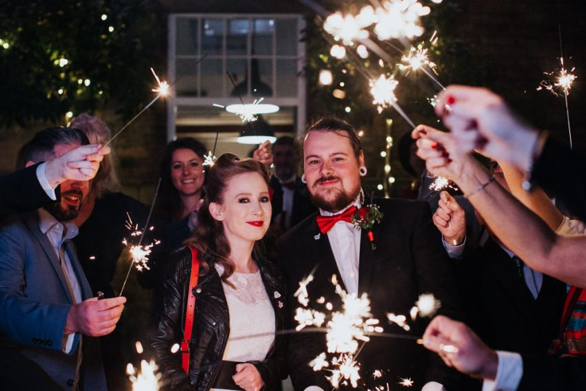 Bride and groom surrounded by guests holding sparklers.