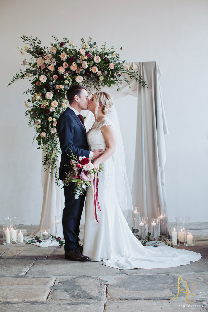 Halifax wedding venue. Bride and groom stood in front of flower arch at the Arches.