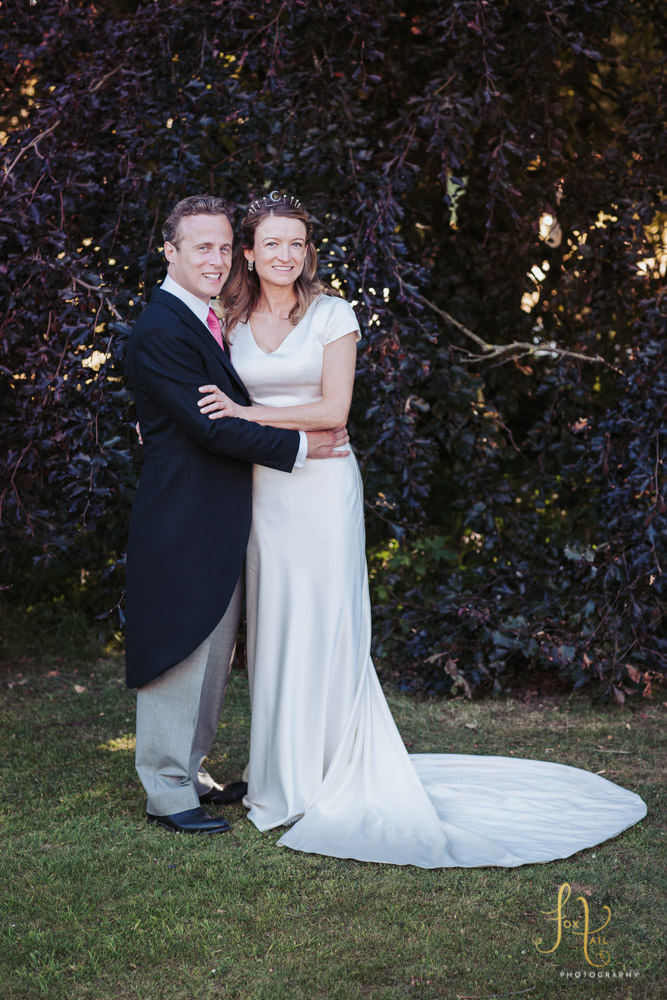Bride wears Emma Victoria Payne dress and groom wears Favourbrook jacket, posed in front of tree.