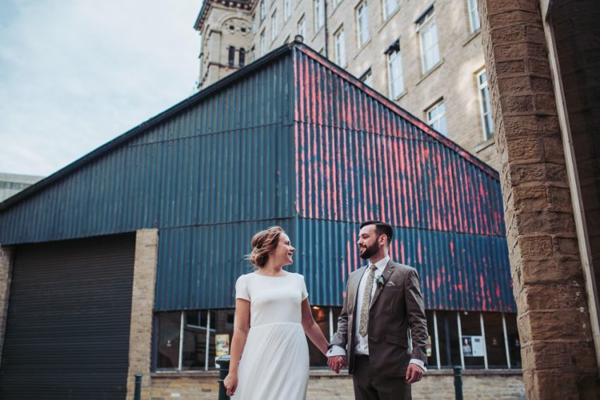 Arches wedding photography. Bride and groom hold hands at Arches wedding photographer. Bride and groom at Yorkshire industrial mill venue.