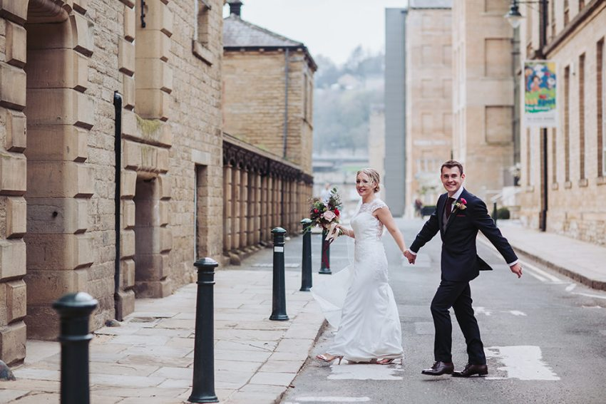 Bride and groom hold hands crossing road at Dean Clough mill wedding venue.