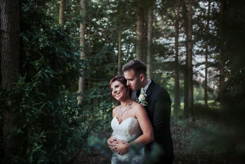 Newly wed couple embrace in woodland surroundings at Forest Pines Hotel in Scunthorpe.
