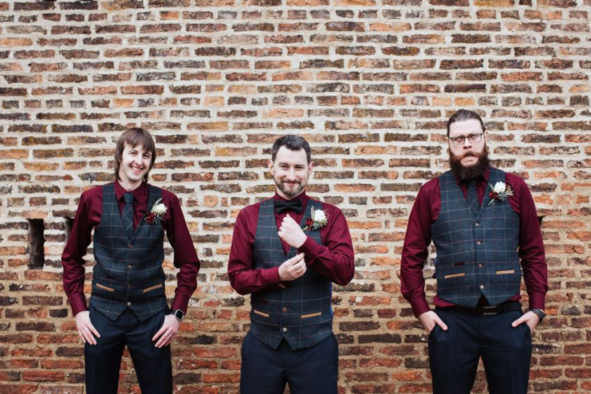 Alternative groomsmen in deep red shirts with tweed waistcoats.